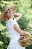 Carefree woman with a straw hat. And wicker basket full of fruit Royalty Free Stock Photo