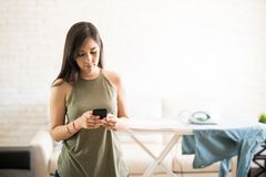 Serious woman texting on mobile phone with iron on clothes in ba. Carefree woman using mobile phone forgetting about the iron on the ironing board Stock Photography