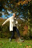 Carefree woman walking in the park and kicking a puddle of water Stock Photo