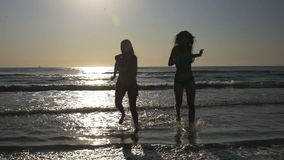 Carefree women dancing on the shore and running towards a sandy beach in slow motion. Carefree women dancing on the shore and running towards the sandy beach in stock footage