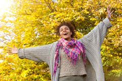 Carefree young african american woman with arms outstretched. Portrait of a carefree young african american woman with arms outstretched outdoors in autumn stock photos