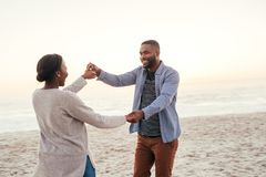Carefree young African couple dancing together at the beach. Carefree young African couple smiling and dancing hand in hand together on a sandy beach at dusk royalty free stock photos