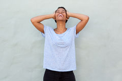 Carefree young black woman laughing with hands behind head Stock Photography