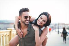 Carefree young caucasian couple in city doing piggyback at outdoors stock photos