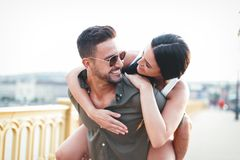 Carefree young caucasian urban couple doing piggyback at outdoors royalty free stock photos
