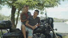 Young couple enjoying leisure on motorbike in park. Carefree young couple enjoying summer leisure on motorcycle in public park. Laughing playful cute teenage stock video footage