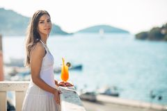 Carefree young female on holiday summer vacation having fun on a sunny day,relaxing with ocean view,listening waves. Enjoying summer with refreshing drink.Love Stock Images