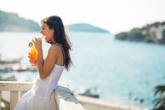 Carefree young female on holiday summer vacation having fun on a sunny day,relaxing with ocean view,listening waves. Enjoying summer with refreshing drink.Love Royalty Free Stock Photo