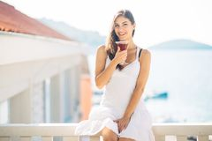 Carefree young female on holiday summer vacation having fun on a sunny day,relaxing with ocean view,listening waves. Enjoying summer with refreshing drink.Love Stock Photo