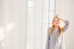 Carefree young female with tousled hair standing near window Royalty Free Stock Photography
