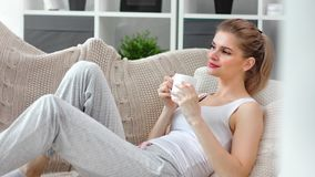 Carefree young girl relaxing on couch drinking coffee from white mug enjoying serenity at cozy home. Medium shot. Beautiful woman housewife drink tea hot stock footage