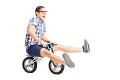 Carefree young guy riding a small bike. Isolated on white background Stock Photos