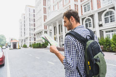 Carefree young guy traveling around town. Cheerful male tourist is walking in city. He is reading map and smiling. Man is carrying backpack Stock Photos