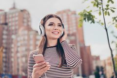 Carefree young lady is listening to favourite song on her smartphone outdoors, walking on the spring street, wearing cozy outfit,. Modern headphones Stock Photography
