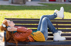 Carefree young lady lying on bench and listening to music Stock Photography