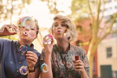 Carefree young lesbian couple blowing bubbles outside in the city. Smiling young lesbian couple having fun blowing bubbles together with a bubble wand while stock photo