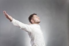 Carefree young man. Side view of carefree young man or free spirit with outstretched arms, light studio background with copy space royalty free stock photography