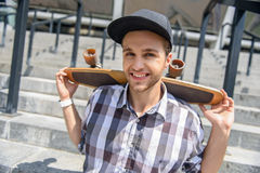 Carefree young man carrying skateboard. Happy male skateboarder is sitting on stairs and carrying skate on his shoulders. He is looking at camera and smiling Royalty Free Stock Photo