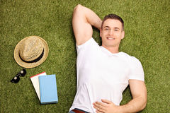 Carefree young man lying on grass. And looking at the camera with a pair of sunglasses, a hat and a couple of books beside him Stock Image