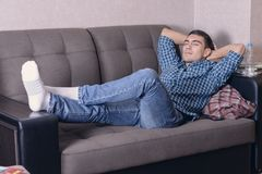 Carefree young man relaxed on the couch with his hands behind his head, dreaming of the future.  Stock Image