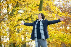 Carefree young man standing outdoors with open arms. Portrait of a carefree young man standing outdoors with open arms Royalty Free Stock Photos
