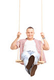 Carefree young man swinging on a swing. Vertical shot of a carefree young man swinging on a wooden swing and looking at the camera isolated on white background Stock Image