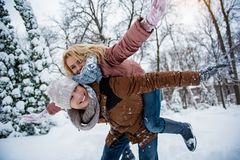 Carefree young man and woman playing in forest. We are free. Joyful loving couple is having fun in winter park. Guy is keeping girl on back and laughing. They Stock Photos