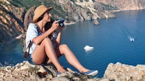 Carefree young travel woman having positive emotion taking picture using camera admiring sea landscape. At sunset. Smiling hiker female relaxing sitting on top stock video