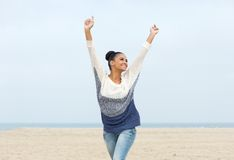 Carefree young woman with arms outstretched walking on the beach Royalty Free Stock Images
