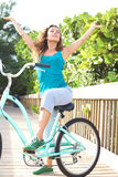 Carefree Young Woman On Bike At The Beach. Full length portrait of carefree young woman sitting on bicycle with arms out. Vertical shot Royalty Free Stock Image
