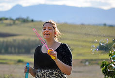 Carefree young woman blowing bubbles in country Royalty Free Stock Image