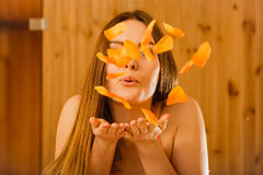Carefree young woman blowing petals in sauna. Royalty Free Stock Photography
