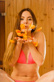 Carefree young woman blowing petals in sauna. Stock Photo