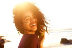 Carefree young woman with curly hair laughing outdoors Royalty Free Stock Photography