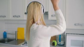 Carefree young woman dancing in kitchen listening to music. Holding smartphone, slowmotion stock footage