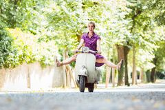 Carefree young woman driving scooter. Happy carefree young woman driving retro scooter stock image