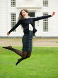 Carefree young woman jumping outdoors. Portrait of a carefree young woman jumping outdoors Royalty Free Stock Photo