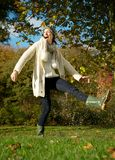 Carefree young woman kicking puddle of water in the park. Portrait of a carefree young woman kicking puddle of water in the park Royalty Free Stock Photography