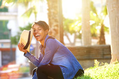 Carefree young woman laughing outside. Side portrait of a carefree young woman laughing outside Royalty Free Stock Photos