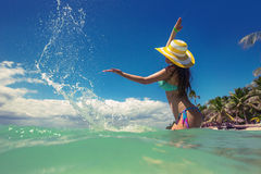 Carefree young woman playing with the water on tropical beach Royalty Free Stock Images