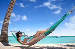 Carefree young woman relaxing on tropical beach Royalty Free Stock Image