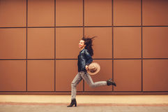 Carefree young woman. Running near the wall stock photos