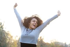 Carefree young woman smiling with arms raised Stock Photo