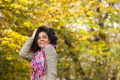 Carefree young woman smiling outdoors. Portrait of a carefree young woman smiling outdoors with hand in hair Stock Photos