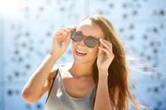 Carefree young woman smiling with sunglasses Stock Photo