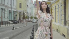 Carefree young woman wearing summer dress with shopping bags in hands trying to catch the taxi in the street of an old. Carefree young woman in a light dress stock video footage