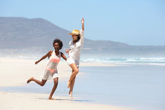 Carefree young women walking barefoot on beach Stock Images