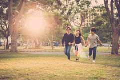 Carefree youth. Friends holding hands when running in city park Royalty Free Stock Photos
