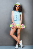Carefree youth. Full length of attractive young African woman holding colorful skateboard and smiling while standing against grey background Royalty Free Stock Image