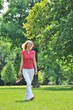 Carefree youth - walking in park. Smiling young woman holding her shoes and walking barefoot on grass in park Royalty Free Stock Image
